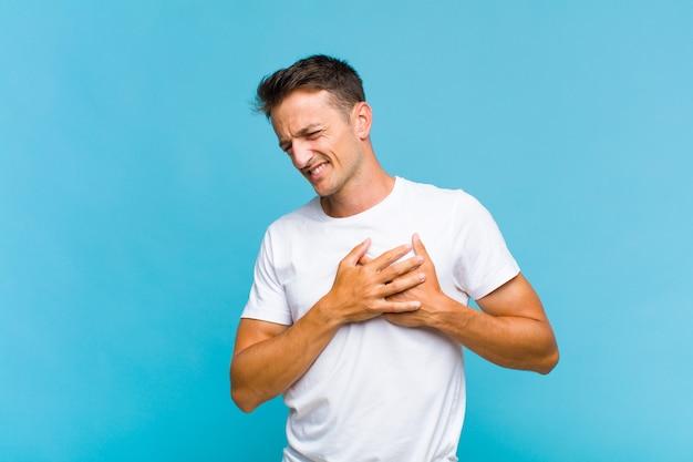 Młody przystojny mężczyzna wyglądający na smutnego, zranionego i załamanego, trzymający obie ręce blisko serca, płaczący i przygnębiony