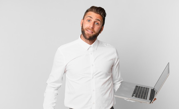 Młody przystojny mężczyzna wyglądający na szczęśliwego i mile zaskoczony i trzymający laptopa