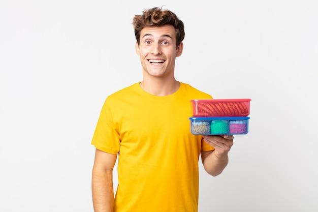 Młody przystojny mężczyzna wyglądający na szczęśliwego i mile zaskoczony i trzymający pudełka na lunch