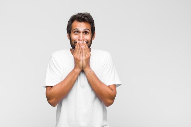 Młody przystojny mężczyzna wyglądający na szczęśliwego i podekscytowanego, zszokowany niespodziewaną niespodzianką z otwartymi obiema rękami obok twarzy