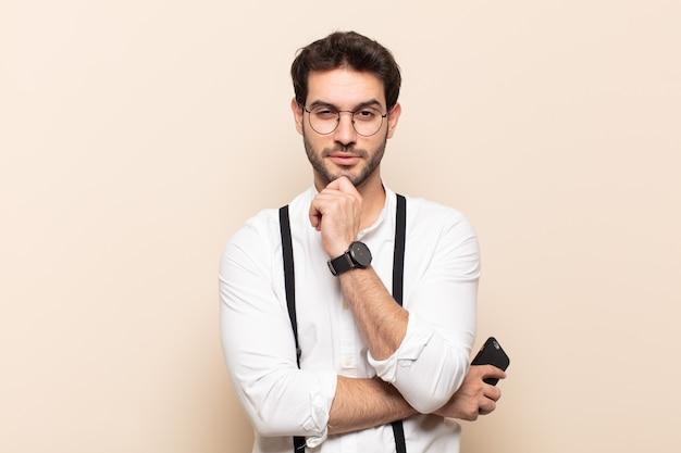 Młody przystojny mężczyzna wyglądający na szczęśliwego i uśmiechniętego z ręką na brodzie, zastanawiający się lub zadający pytanie, porównujący opcje