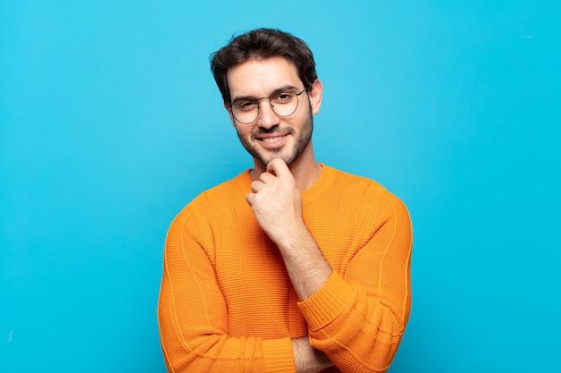 Młody przystojny mężczyzna wyglądający na szczęśliwego i uśmiechnięty z ręką na brodzie, zastanawiający się lub zadający pytanie, porównujący opcje