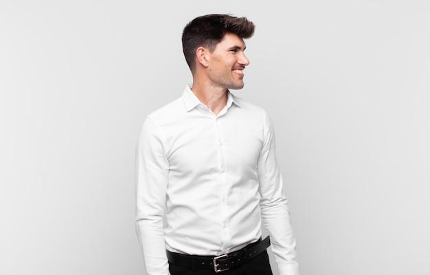 Młody przystojny mężczyzna wyglądający na szczęśliwego, wesołego i pewnego siebie, uśmiechającego się dumnie i patrzącego w bok z obiema rękami na biodrach