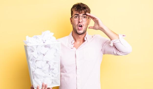 Młody przystojny mężczyzna wyglądający na szczęśliwego, zdziwionego i zdziwionego. koncepcja kosza z kulkami papierowymi