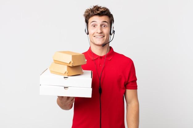 Młody przystojny mężczyzna wyglądający na szczęśliwy i mile zaskoczony. koncepcja fast foodów na wynos