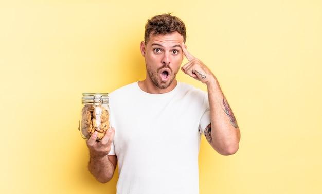 Młody przystojny mężczyzna wyglądający na zaskoczonego, realizujący nową myśl, pomysł lub koncepcję koncepcji butelki ciasteczek