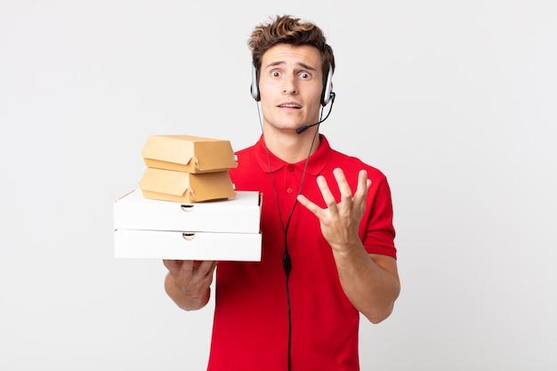 Młody przystojny mężczyzna wyglądający na zdesperowanego, sfrustrowanego i zestresowanego. koncepcja fast foodów na wynos