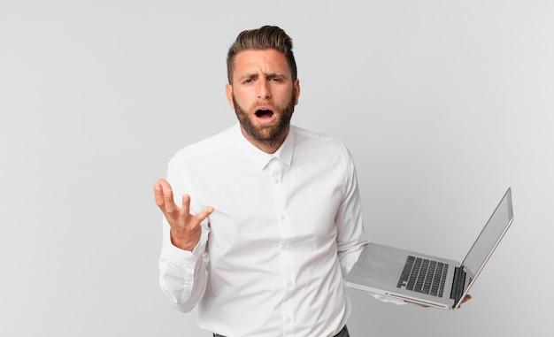 Młody przystojny mężczyzna wyglądający na zdesperowanego, sfrustrowanego i zestresowanego, trzymający laptopa