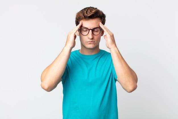 Młody przystojny mężczyzna wyglądający na zestresowanego i sfrustrowanego, pracujący pod presją, z bólem głowy i z problemami