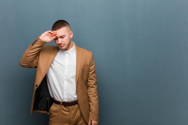 Młody przystojny mężczyzna wyglądający na zestresowanego, zmęczonego i sfrustrowanego, osusza pot z czoła, czuje się beznadziejny i wyczerpany przy płaskiej ścianie