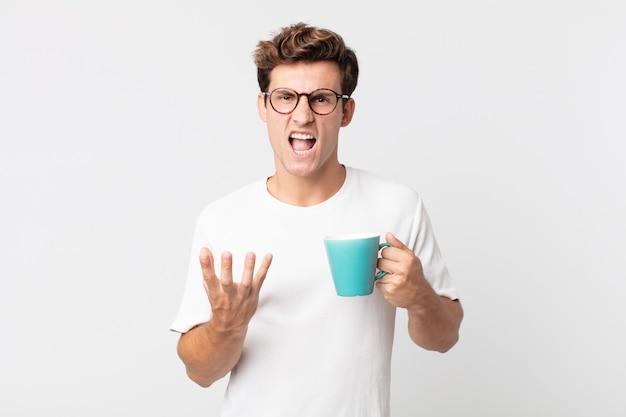 Młody przystojny mężczyzna wyglądający na złego, zirytowanego i sfrustrowanego, trzymający filiżankę kawy