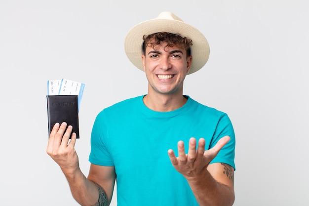 Młody przystojny mężczyzna wyglądający na zły, zirytowany i sfrustrowany. podróżnik trzymający paszport