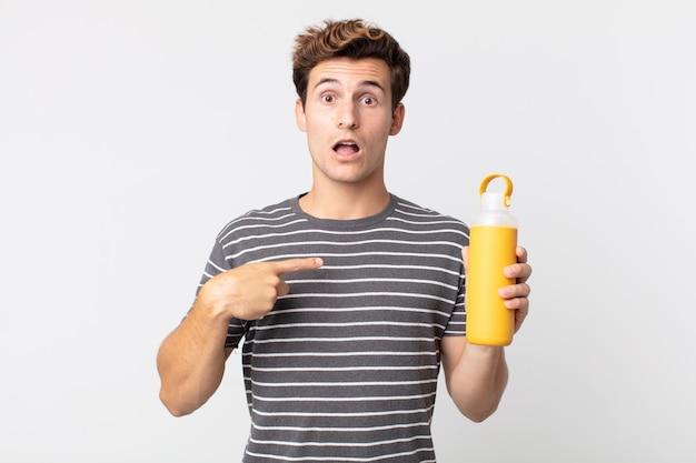 Młody przystojny mężczyzna wyglądający na zszokowanego i zaskoczonego z szeroko otwartymi ustami, wskazujący na siebie i trzymający termos z kawą