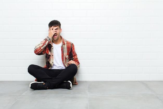 Młody przystojny mężczyzna wyglądający na zszokowanego, przestraszonego lub przerażonego, zakrywający twarz dłonią i zerkający między palcami na cementowej podłodze