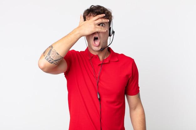 Młody przystojny mężczyzna wyglądający na zszokowanego, przestraszonego lub przerażonego, zakrywający twarz dłonią. koncepcja telemarketera