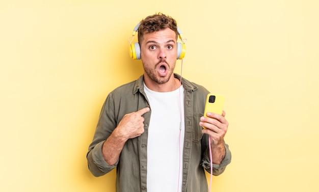 Młody przystojny mężczyzna wyglądający na zszokowany i zaskoczony z szeroko otwartymi ustami, wskazujący na własne słuchawki i koncepcję smartfona