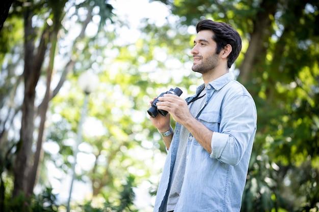Młody przystojny mężczyzna wyglądający naturalnie i używając lornetki w publicznym parku z szczęśliwą twarzą stojącą i uśmiechniętą