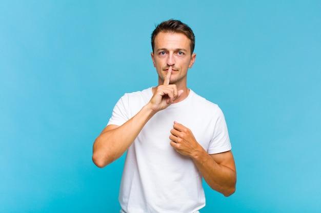 Młody przystojny mężczyzna wyglądający poważnie i krzywo z palcem przyciśniętym do ust, domagający się ciszy lub spokoju, zachowujący tajemnicę