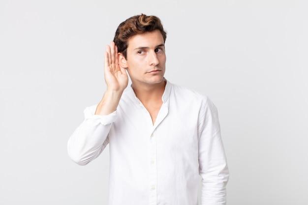 Młody przystojny mężczyzna wyglądający poważnie i zaciekawiony, słuchający, próbujący usłyszeć tajną rozmowę lub plotki, podsłuchujący