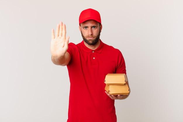 Młody przystojny mężczyzna wyglądający poważnie pokazując otwartą dłoń robiący gest zatrzymania burger dostarczający koncepcję