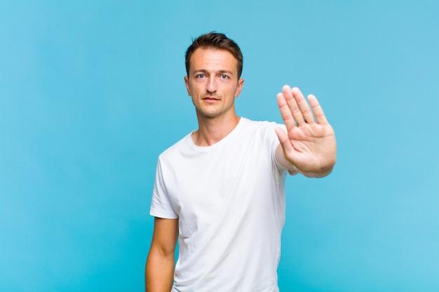 Młody przystojny mężczyzna wyglądający poważnie, surowo, niezadowolony i zły pokazując otwartą dłoń wykonujący gest stop
