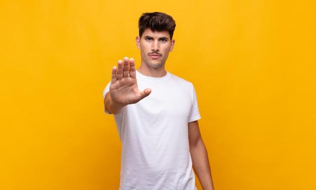 Młody przystojny mężczyzna wyglądający poważnie, surowo, niezadowolony i zły, pokazując otwartą dłoń wykonujący gest stopu