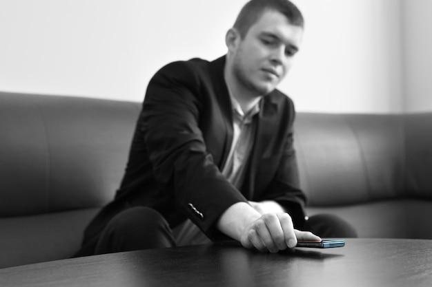 Młody przystojny mężczyzna wykonawczy umieszczając swój telefon komórkowy na stole w salonie. uchwycony w skali szarości.