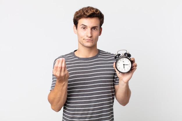 Młody przystojny mężczyzna wykonujący gest kaprysu lub pieniędzy, mówiący ci, aby zapłacić i trzymający budzik