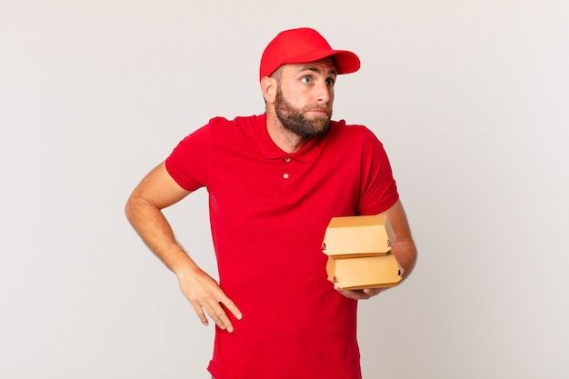 Młody przystojny mężczyzna wzrusza ramionami, czuje się zdezorientowany i niepewny, dostarczając koncepcję burgera