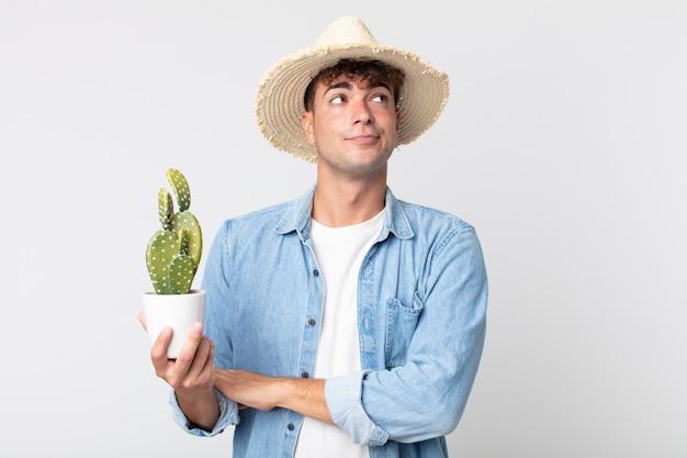 Młody przystojny mężczyzna wzrusza ramionami, czuje się zdezorientowany i niepewny. rolnik trzymający ozdobnego kaktusa