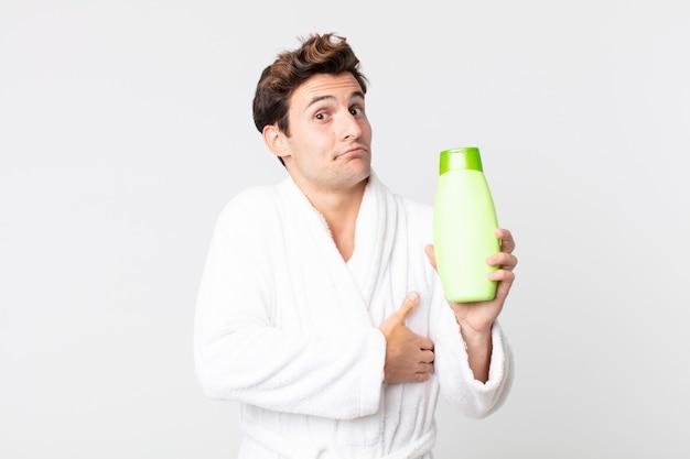Młody przystojny mężczyzna wzrusza ramionami, czuje się zdezorientowany i niepewny w szlafroku i trzyma butelkę szamponu