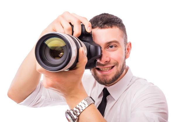 Młody przystojny mężczyzna z aparatem na białym tle nad białą ścianą.