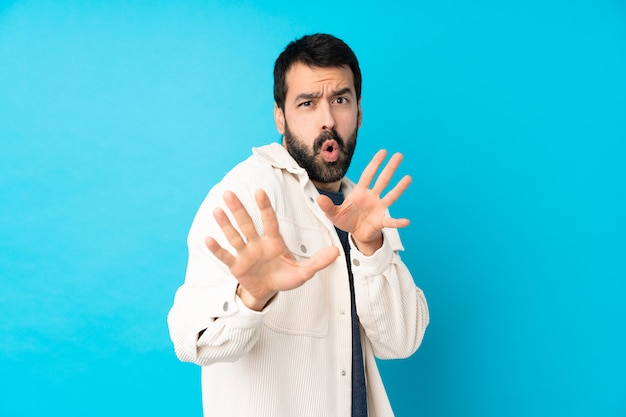 Młody przystojny mężczyzna z białą sztruksową kurtką na pojedyncze nerwowe niebieskie ściany rozciągające ręce do przodu