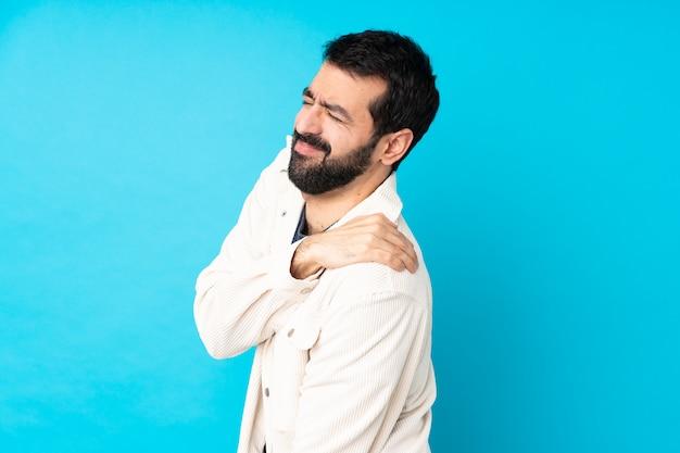 Młody przystojny mężczyzna z białą sztruksową kurtką nad odosobnioną błękit ścianą cierpi z powodu bólu w ramieniu za to, że podjął wysiłek