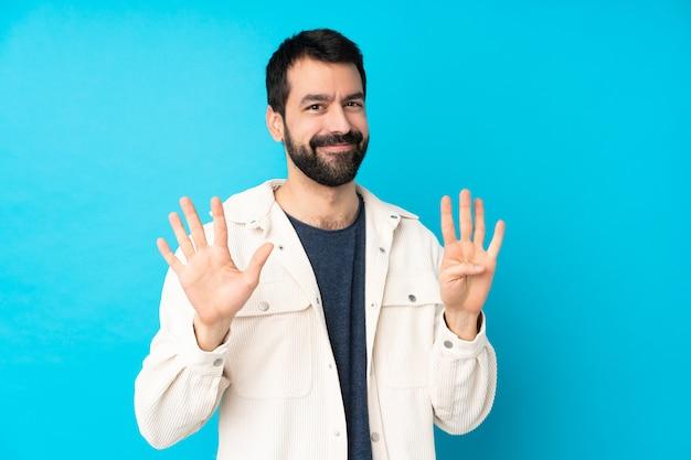 Młody przystojny mężczyzna z białą sztruksową kurtką nad odosobnioną błękit ścianą liczy dziewięć z palcami