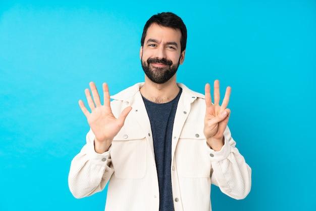 Młody przystojny mężczyzna z białą sztruksową kurtką nad odosobnioną błękit ścianą liczy osiem z palcami