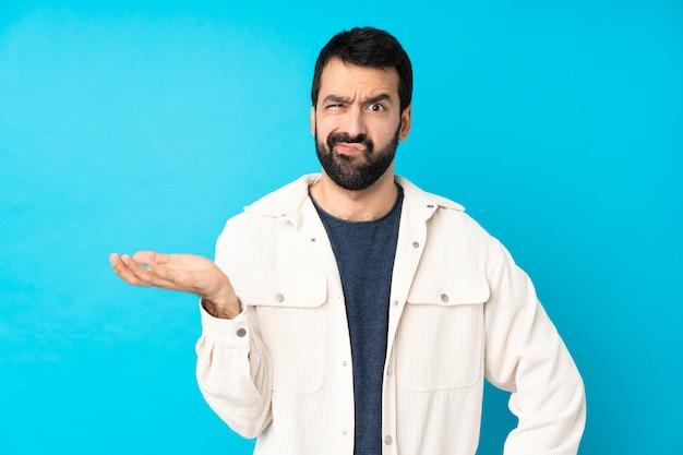 Młody przystojny mężczyzna z białą sztruksową kurtką nad odosobnioną błękit ścianą nieszczęśliwy dla nie rozumie czegoś