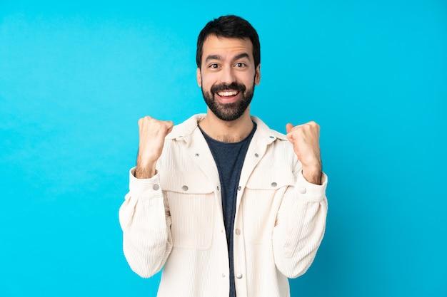 Młody przystojny mężczyzna z białą sztruksową kurtką nad odosobnioną błękit ścianą świętuje zwycięstwo w zwycięzca pozyci