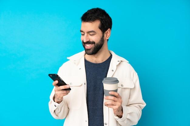 Młody przystojny mężczyzna z białą sztruksową kurtką nad odosobnioną błękit ścianą trzyma kawę zabrać i wiszącą ozdobę