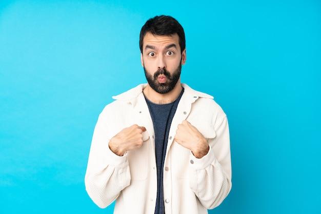 Młody przystojny mężczyzna z białą sztruksową kurtką nad odosobnioną błękit ścianą wskazuje ja