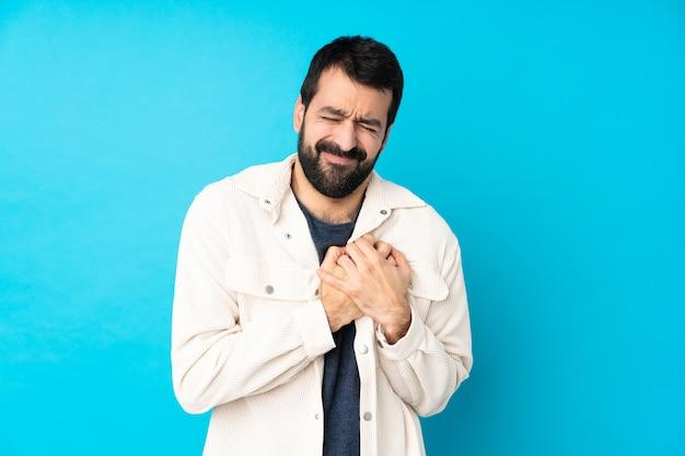 Młody przystojny mężczyzna z białą sztruksową kurtką nad odosobnionym błękitem