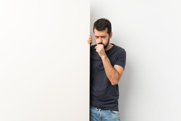 Młody przystojny mężczyzna z brodą cierpi na kaszel i źle się czuje