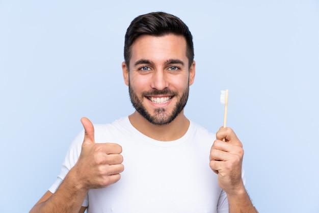 Młody przystojny mężczyzna z brodą myje zęby kciukami do góry, ponieważ stało się coś dobrego