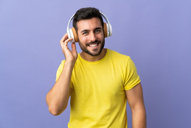 Młody przystojny mężczyzna z brodą na białym tle na fioletowym tle słuchania muzyki