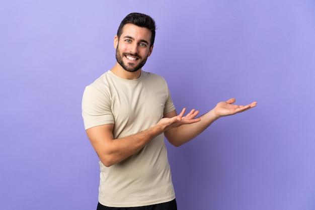 Młody przystojny mężczyzna z brodą na izolowanej ścianie wyciągając ręce na bok za zaproszenie