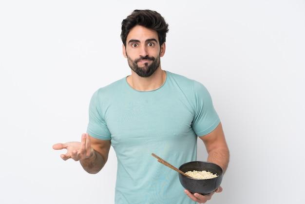 Młody przystojny mężczyzna z brodą na pojedyncze białe ściany co gest wątpliwości, podnosząc ramiona, trzymając miskę makaronu pałeczkami