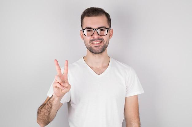 Młody przystojny mężczyzna z brodą na sobie casualową koszulkę, stojąc przed białą ścianą, uśmiechając się z radosną miną, czyniąc znak zwycięstwa.