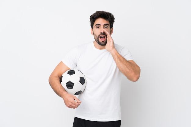 Młody przystojny mężczyzna z brodą nad odosobnioną biel ścianą krzyczy z usta szeroko otwarty