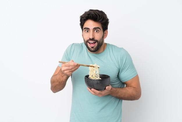 Młody przystojny mężczyzna z brodą nad odosobnioną biel ścianą trzyma puchar kluski z pałeczkami i je je