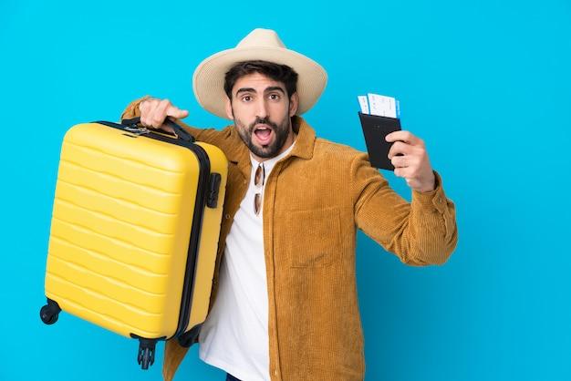 Młody przystojny mężczyzna z brodą nad odosobnioną błękit ścianą w wakacje z walizką i paszportem i zaskakujący